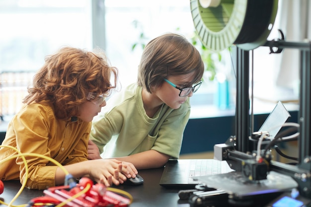 Портрет двух мальчиков, использующих 3d-принтер во время урока инженерии и робототехники в школе, копия пространства