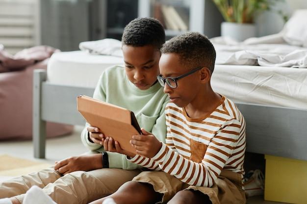 Портрет двух мальчиков, использующих планшет вместе, сидя на полу дома и смотря видео