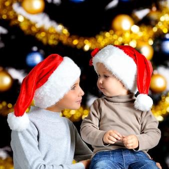 お互いを見つめている新年のサンタの帽子の2人の兄弟の肖像画-屋内