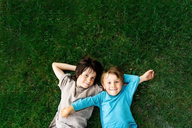 공원에서 잔디에 누워 두 형제의 초상화. 야외에서 웃는 행복한 아이들. 형제 자매 우정.