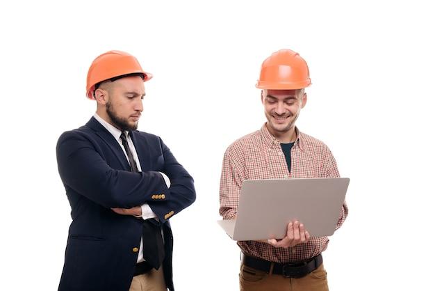 白い孤立した背景の上に立って、ラップトップのディスプレイを見ている保護オレンジ色のヘルメットの2人のビルダーの肖像画。建設プロジェクトについて話し合う