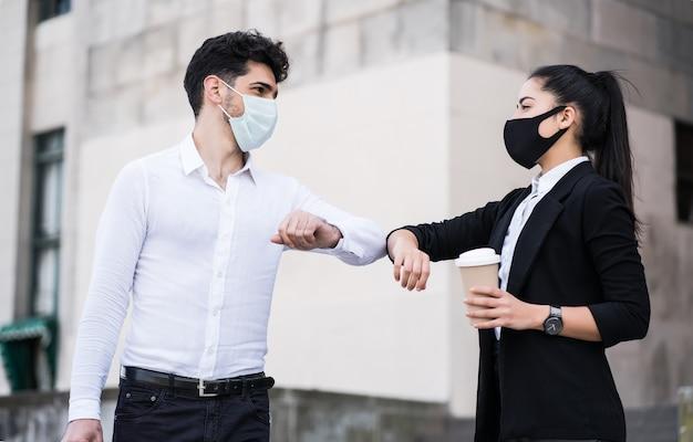 屋外でお互いに挨拶するために肘をぶつけている2人のビジネスマンの肖像画。ビジネスコンセプト。新しい通常のライフスタイルのコンセプト。