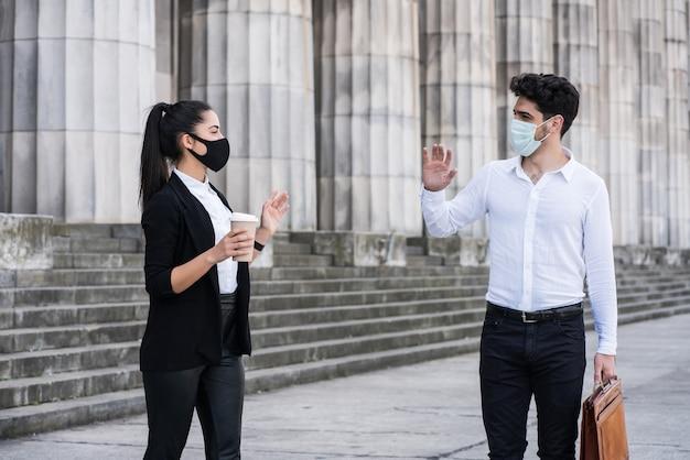 屋外で社会的な距離を保ちながら挨拶するために手を振っている2つのビジネスの肖像画。ビジネスコンセプト。新しい通常のライフスタイルのコンセプト。