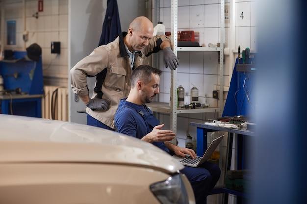 Портрет двух автомехаников, использующих ноутбук во время работы в мастерской по ремонту автомобилей, копировальное пространство
