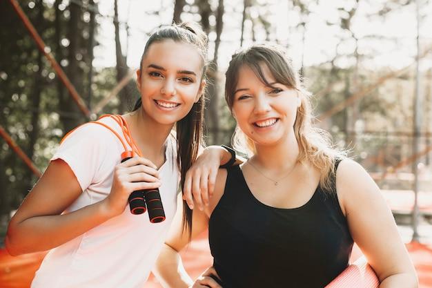Портрет двух очаровательных женщин, глядя на камеру, смеясь после утренней спортивной рутины.