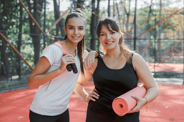 Портрет двух очаровательных молодых женщин, улыбаясь, делая упражнения по утрам для похудения.