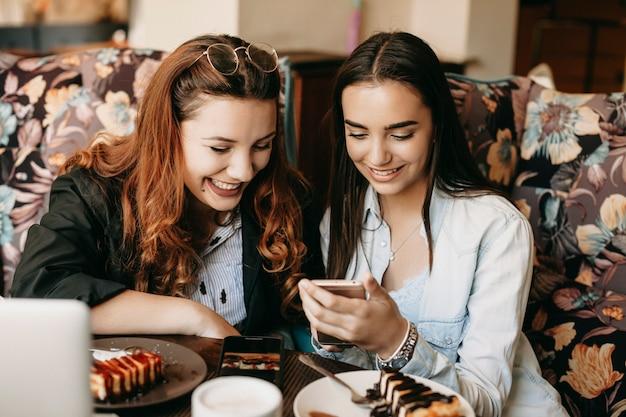 Портрет двух веселых друзей, глядя на экран смартфона, улыбаясь, сидя в кафе, есть чизкейк и пить кофе.