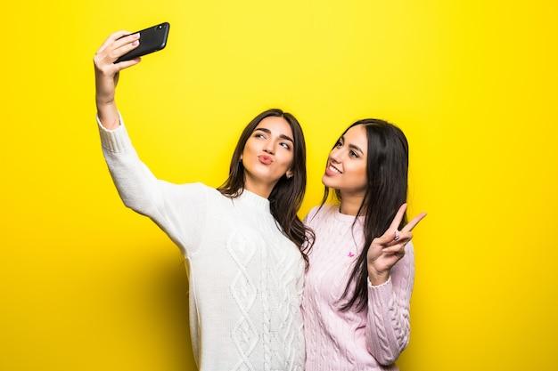 서서 노란색 벽 위에 고립 된 셀카를 복용 스웨터를 입은 두 명랑 소녀의 초상화