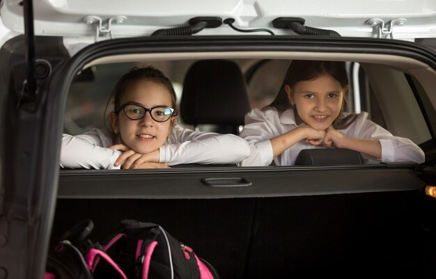 Портрет двух веселых девушек, сидящих в машине и смотрящих через заднюю сторону