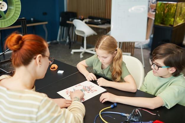 Портрет двух детей, смотрящих на схемы и планы во время урока инженерии и робототехники в современной школе, копировальное пространство