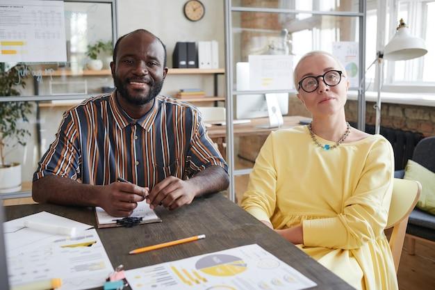 Портрет двух коллег, улыбающихся в камеру, обсуждая финансовые документы за столом во время встречи