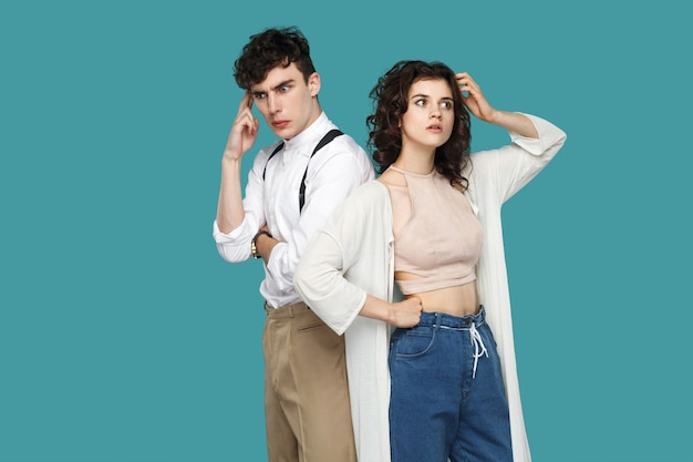 Портрет двух смущенных вдумчивых брюнеток стильных партнеров, стоящих, глядя в сторону, почесывая голову и думая, что делать и пытаясь найти ответ. крытая студия выстрел, изолированные на синем фоне.