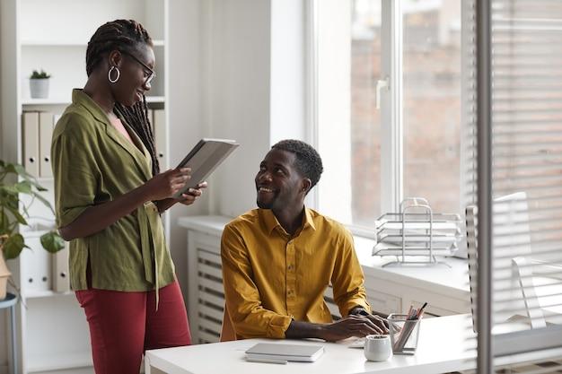 Портрет двух современных афро-американских людей, обсуждающих проект и улыбающихся во время работы в офисе, копией пространства