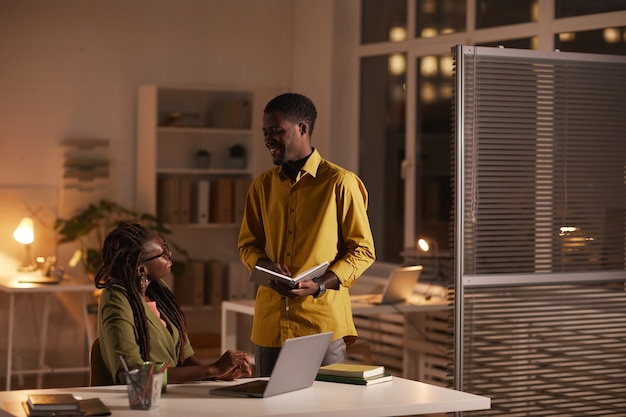 Портрет двух современных афро-американских людей, обсуждающих проект и улыбающихся, работая допоздна в офисе, скопируйте пространство