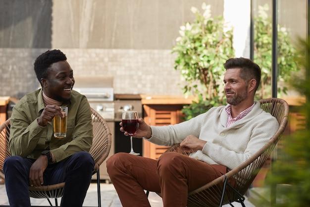 屋外テラスのラウンジチェアでリラックスしながらワインを楽しむ2人の現代的な男性の肖像画、
