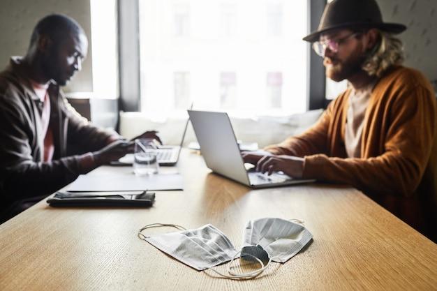 전경에 있는 두 개의 얼굴 마스크, 코비드 개념, 복사 공간에 초점을 맞춘 카페 테이블에서 작업하는 동안 노트북을 사용하는 두 현대 남성의 초상화