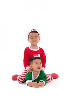 白で隔離されるサンタさんの帽子をかぶって一緒に遊ぶ2つのかわいいアジアの少年のポートレート