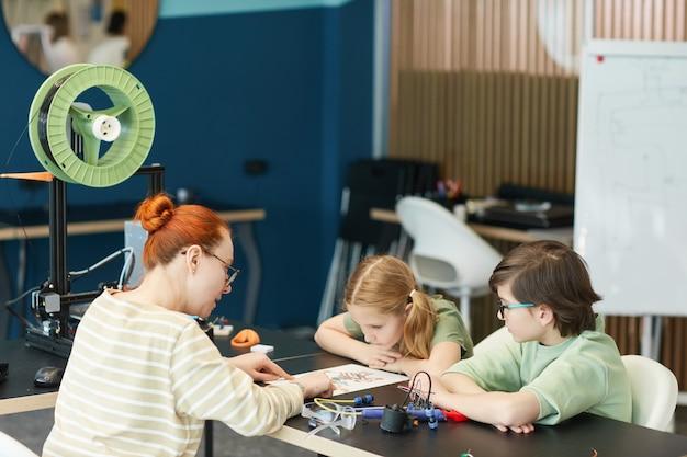 Портрет двух милых детей, слушающих учительницу во время урока инженерии и робототехники в современной школе, копировальное пространство