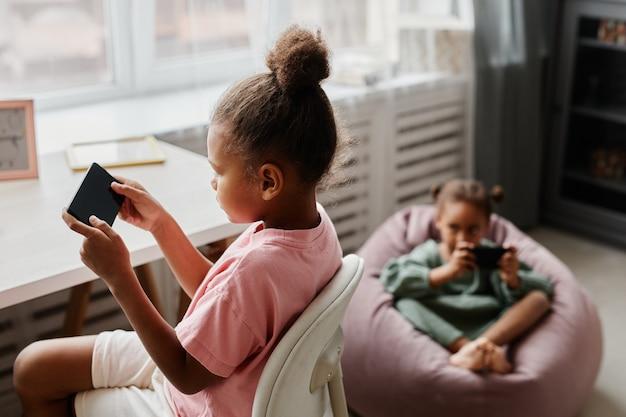 Портрет двух симпатичных девушек, использующих смартфоны и играющих в мобильные игры дома с копией пространства