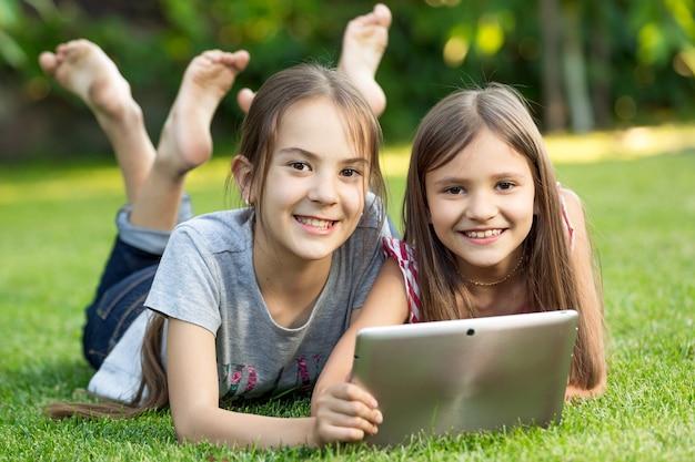 Портрет двух милых улыбающихся девушек, лежащих на траве в парке с цифровым планшетом