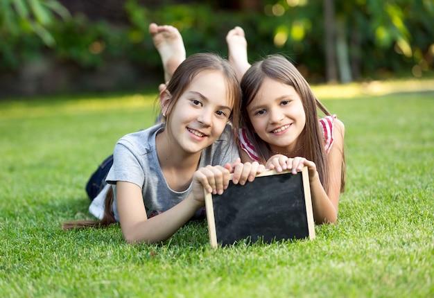 칠판과 잔디에 누워 두 귀여운 웃는 여자의 초상화