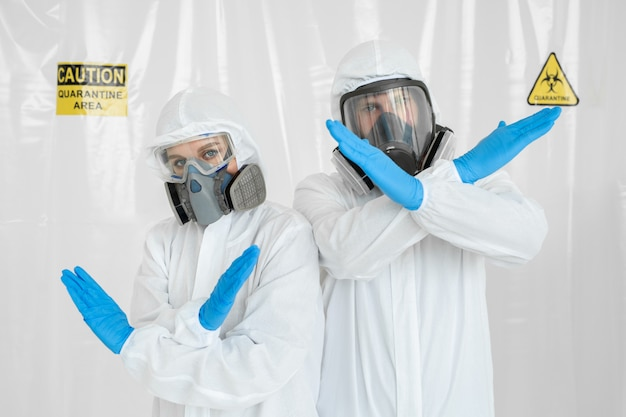 Портрет двух врачей, мужчина и женщина показывают знак остановки коронавируса. молодой врач в медицинской форме с защитной маской и в перчатке показывает знак остановки. коронавирус (covid-19