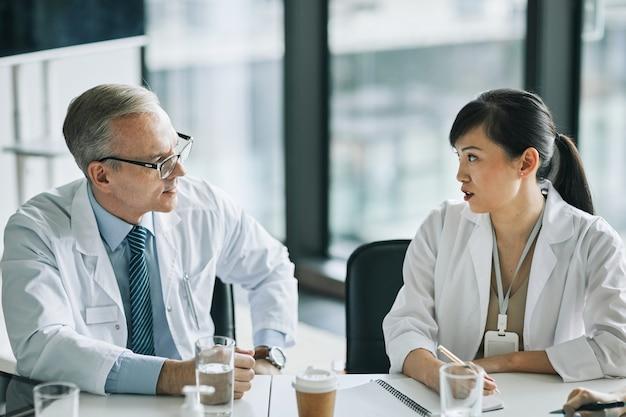 의료 세미나 중 회의실의 회의 테이블에 앉아 있는 두 의사의 초상화