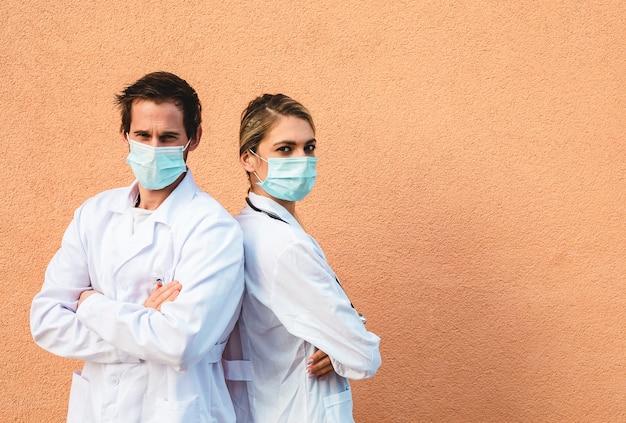 保護マスクを持つ2人の医師の肖像画。カラフルな背景