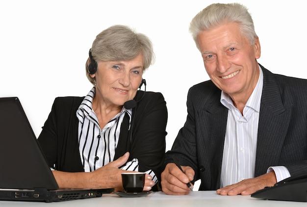 흰색 바탕에 노트북으로 작업하는 두 노인의 초상화