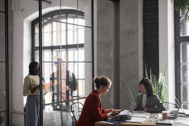 Портрет двух элегантных деловых женщин, работающих вместе в графическом интерьере офиса, копией пространства