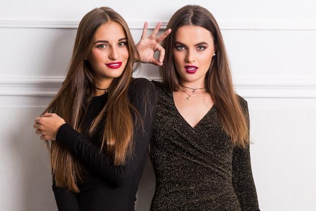 Портрет двух элегантных молодых женщин в гламурных длинных платьях, позирующих на белой стене