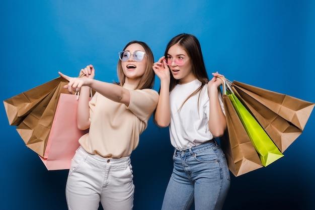 青い壁に隔離されたショッピングバッグを持っている2つの興奮した若い女性の手の肖像画。