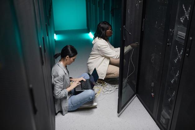 Портрет двух женщин-инженеров по обработке данных, использующих ноутбук в серверной и настраивающих суперкомпьютерную сеть, копировальное пространство