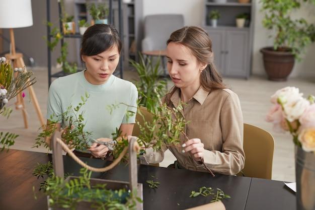 装飾、コピースペースのための花の構成を作成しながら緑の植物を保持している2人の女性の花屋の肖像画