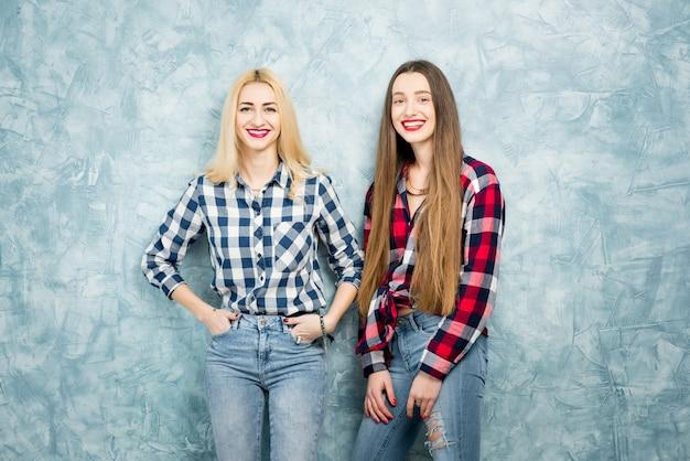 青い塗られた壁の背景に一緒に市松模様のシャツとジーンズの2人の女性の友人の肖像画