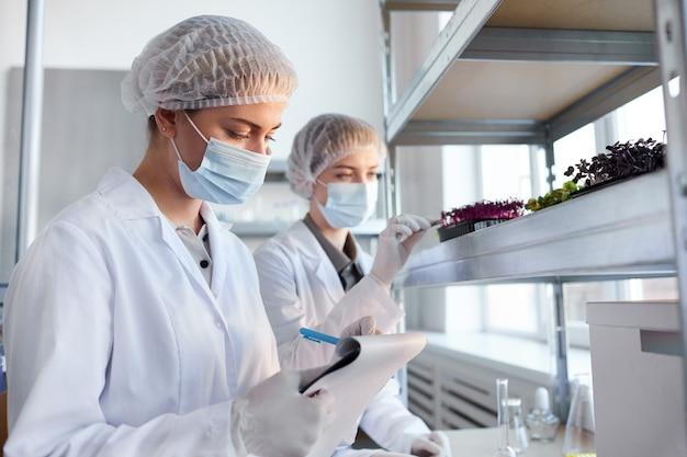 생명 공학 실험실에서 작업하고 클립 보드에 쓰는 동안 식물 샘플을 검사하는 두 여성 과학자의 초상화, 복사 공간