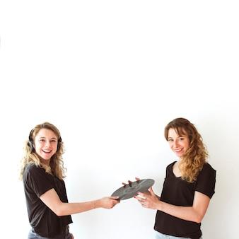 Portrait of two female sister holding vinyl record against white backdrop