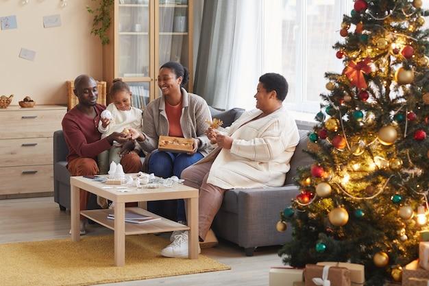 Портрет двух поколений афро-американской семьи, вместе украшающей дом на рождество, наслаждаясь праздничным сезоном в уютной атмосфере, копируя пространство