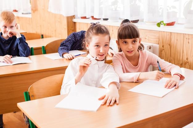 교실에서 같은 책상에 앉아 있는 두 여자 친구의 초상화