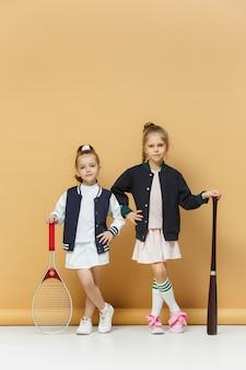 Портрет двух девочек, как теннисисты, держа теннисные ракетки.