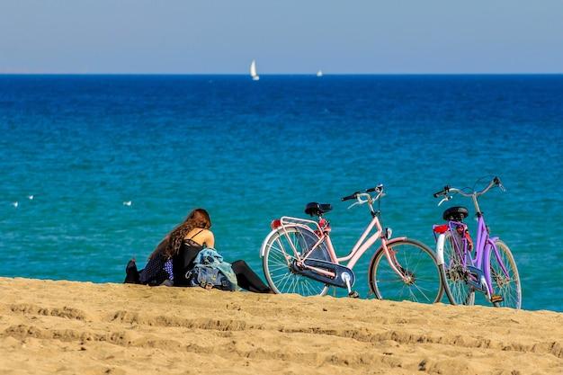자전거와 함께 바다 쪽 모래에 앉아 두 여자 커플의 초상화.