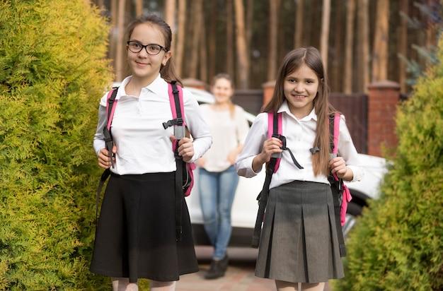 学校でのレッスン後にランドセルでポーズをとる2人の女の子の肖像画