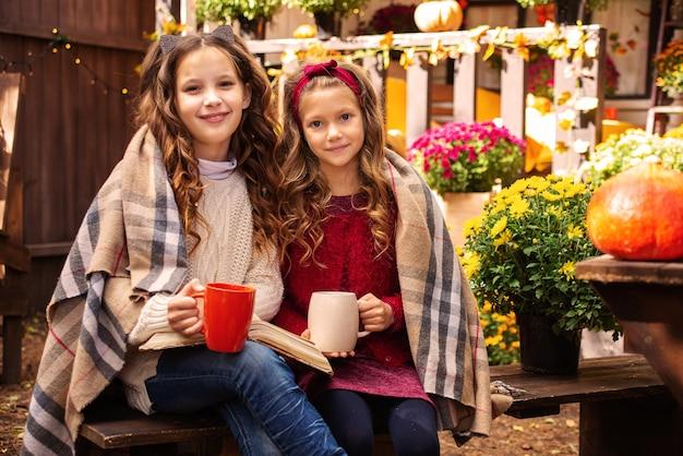 Портрет двух девочек-сестер осенью возле дома