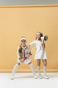 テニスラケットを保持している2人の女の子のテニス選手の肖像画スタジオショットパステルの背景