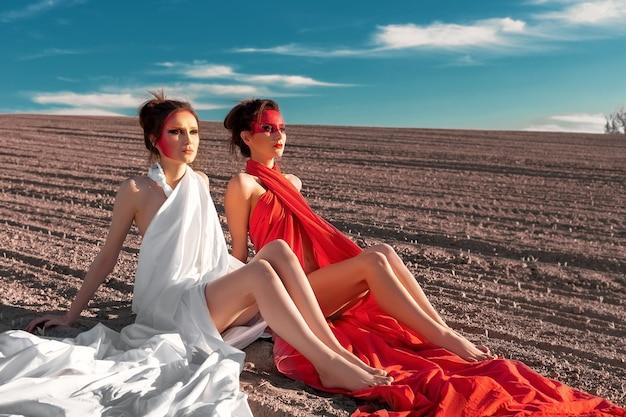 裸の地面に座っている創造的なボディー アートと化粧を持つ 2 人の女の子の肖像画