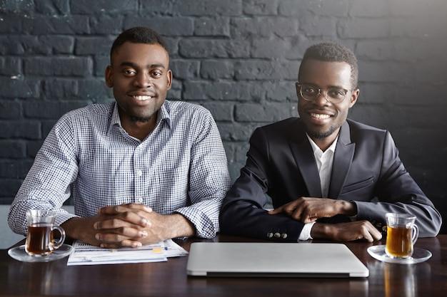 デスクで互いに近くに座っている2人のハンサムな自信を持ってアフリカ系アメリカ人の採用担当者の肖像画