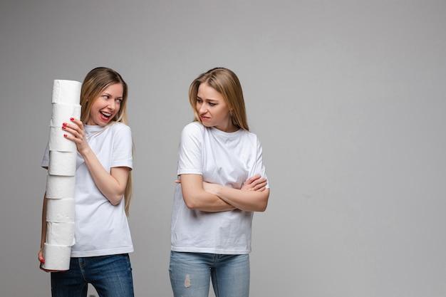 Портрет двух красивых девушек с длинными светлыми волосами, одна из которых держит много туалетной бумаги, а другая обижена изолированно на сером фоне
