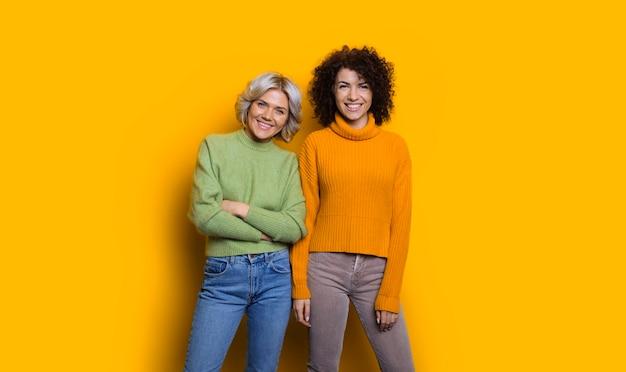 노란색 스튜디오 벽에 고립 된 카메라 웃음을보고 곱슬 머리를 가진 다른 금발 머리를 가진 두 행복 사랑스러운 자매의 초상화.