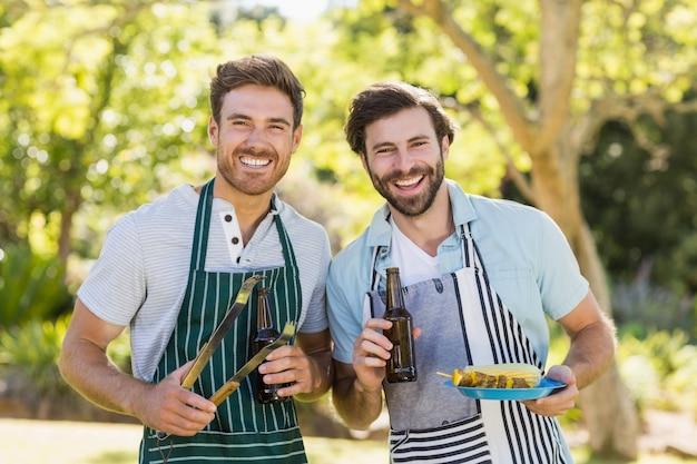 バーベキューの食事とビール瓶を保持している2つの幸せな男性の肖像画