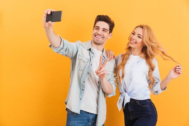 黄色の壁に分離されたピースサインを見せながらスマートフォンでselfie写真を撮る2つの幸せな人の男と女の肖像